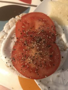 Simple snack of sliced tomato with ground black pepper and ricecake